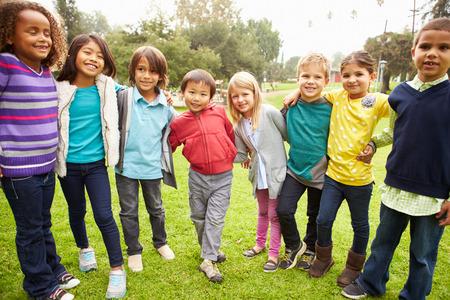 niños jugando en el parque: Grupo de niños jovenes que cuelgan hacia fuera en el parque