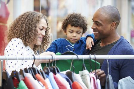 Rodina dívá na oblečení na lištu do nákupního centra