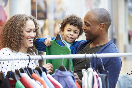 african american woman smiling: Family Looking At Clothes On Rail In Shopping Mall Stock Photo