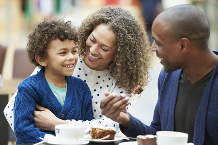Family Enjoying Snack In Caf� Together