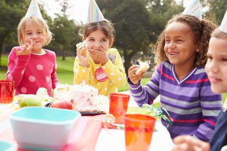 niños sentados: Grupo de niños que tienen fiesta de cumpleaños al aire libre