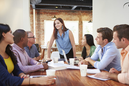 group work: Female Boss Addressing Office Workers At Meeting Stock Photo