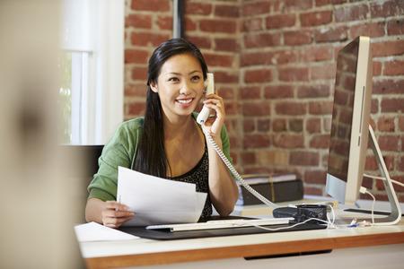 hablando por celular: Mujer trabajando en la computadora en la oficina moderna