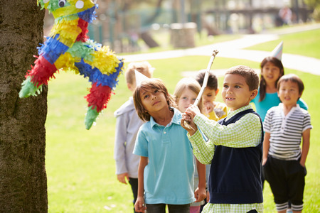 five years old: Children Hitting Pinata At Birthday Party