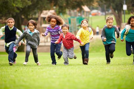 bambini: Gruppo di bambini corre verso la telecamera nel parco