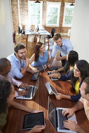 design office: Group Of Office Workers Meeting To Discuss Ideas Stock Photo