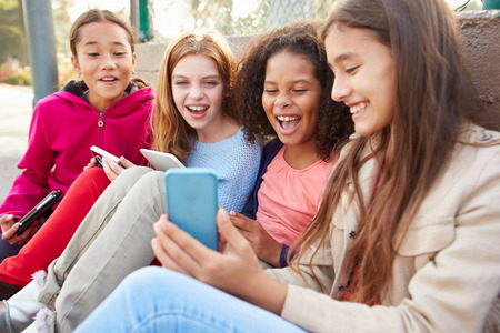 10 11 years: Young Girls Using Digital Tablets And Mobile Phones In Park Stock Photo
