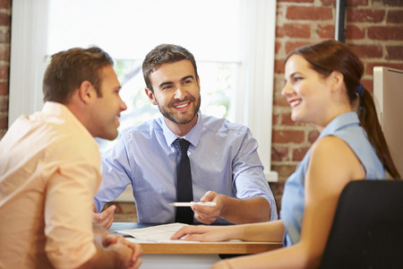 Couple Meeting With Financial Advisor In Office Zdjęcie Seryjne