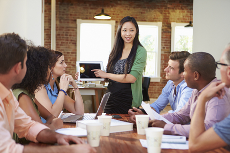 collaborating: Female Boss Addressing Office Workers At Meeting Stock Photo