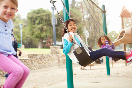Three Young Girls Playing On Swing In Playground