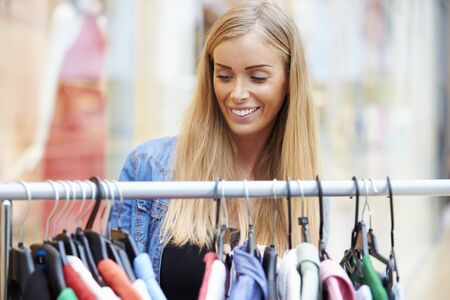 woman clothes: Woman Looking At Clothes On Rail In Shopping Mall Stock Photo