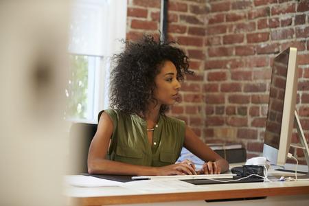 mujer trabajadora: Mujer trabajando en la computadora en la oficina moderna