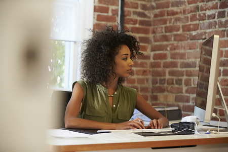 mixed race woman: Woman Working At Computer In Contemporary Office