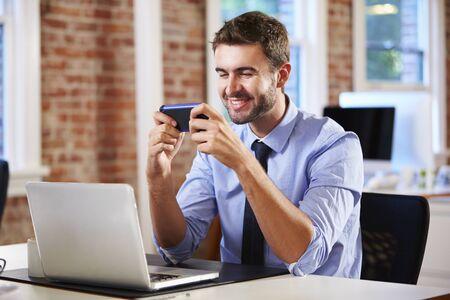 empleado de oficina: El hombre de negocios que usa el teléfono móvil en la oficina creativa Foto de archivo