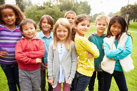 caras felices: Grupo de niños jovenes que cuelgan hacia fuera en el parque