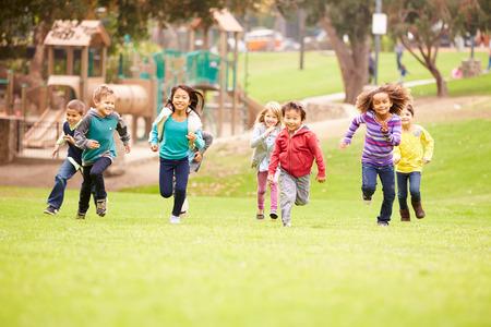 dzieci: Grupa małych dzieci uruchomiony w kierunku kamery w parku