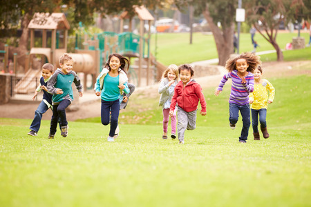 niños en recreo: Grupo de niños jovenes corriendo hacia la cámara en el parque Foto de archivo