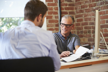 interview: Businessman Interviewing Male Job Applicant In Office