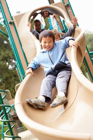 Jonge Jongen spelen op dia in Speelplaats