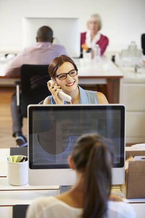 trabajo oficina: El hombre de negocios en el teléfono en la oficina moderna creativa Foto de archivo