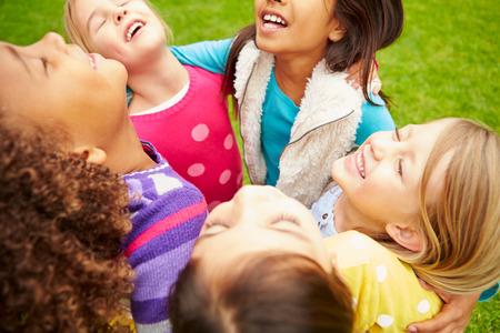 Grupo de chicas jóvenes que cuelgan hacia fuera en el parque Juntos