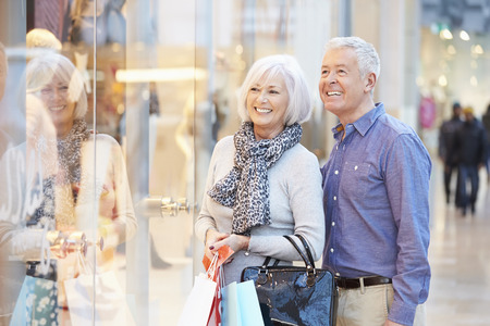 Happy Senior Couple Carrying Bags In Shopping Mall Stock Photo