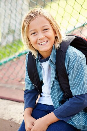 11 years: Portrait Of Young Boy With Rucksack Sitting In Park