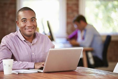 hombre tomando cafe: Hombre Que Trabaja En La Computadora Portátil En Oficina Contemporáneo