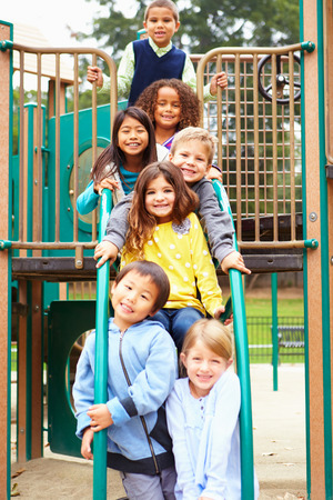niños sentados: Niños pequeños sentado en marco que sube en patio