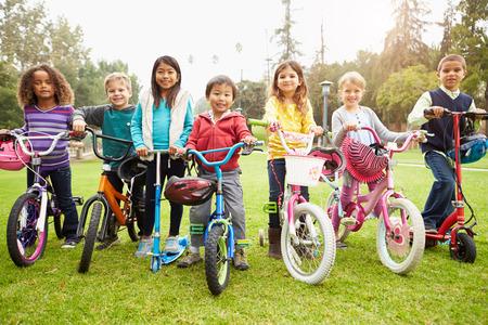 niños en bicicleta: Niños jovenes con las bicis y scooters en el Parque