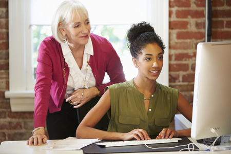 advice: Two Women Working At Computer In Contemporary Office Stock Photo