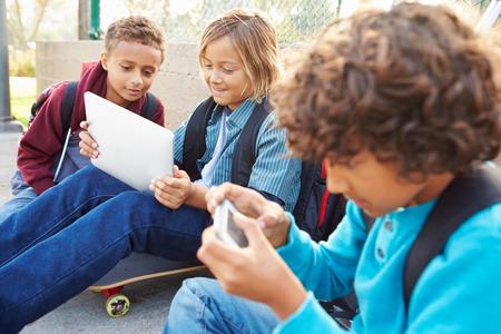 niño con mochila: Young Boys Utilizando tabletas digitales y teléfonos móviles en el parque Foto de archivo
