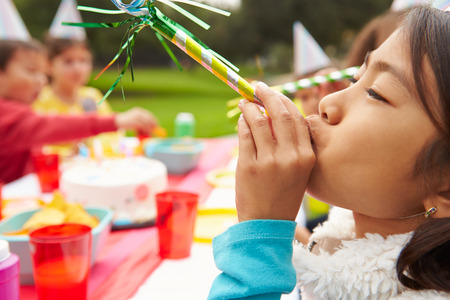 child birthday: Girl With Blower At Outdoor Birthday Party