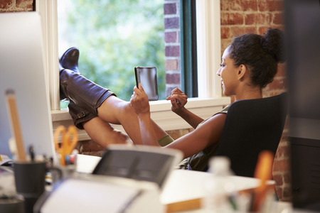 feet up: Businesswoman With Digital Tablet Relaxing In Modern Office
