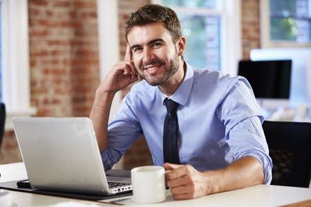 cool people: Man Working At Laptop In Contemporary Office Stock Photo