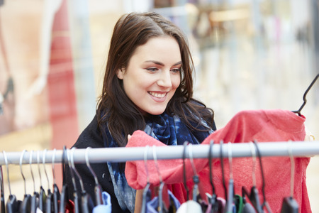 clothes rail: Woman Looking At Clothes On Rail In Shopping Mall Stock Photo