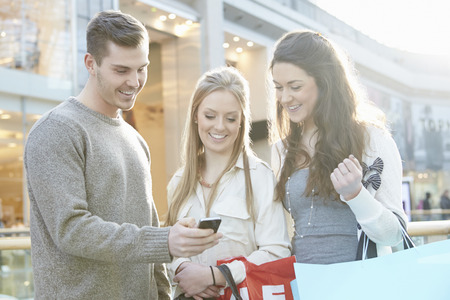 mobile business: Group Of Friends Shopping In Mall Looking At Mobile Phone