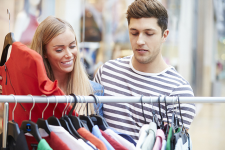 clothing stores: Couple Looking At Clothes On Rail In Shopping Mall