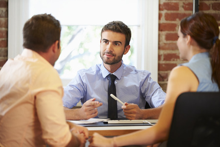 Couple Meeting With Financial Advisor In Office 스톡 콘텐츠