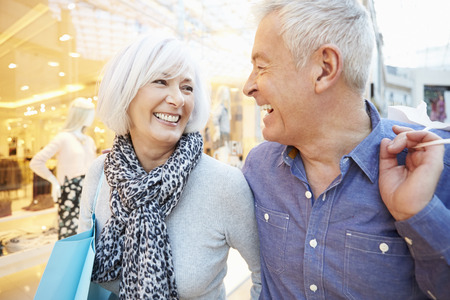 Happy Senior Couple Carrying Bags In Shopping Mall Archivio Fotografico