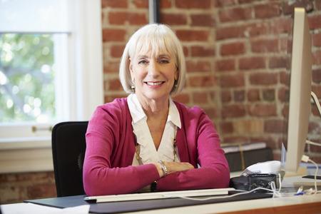 Hogere Vrouw die bij Computer In hedendaagse kantoor