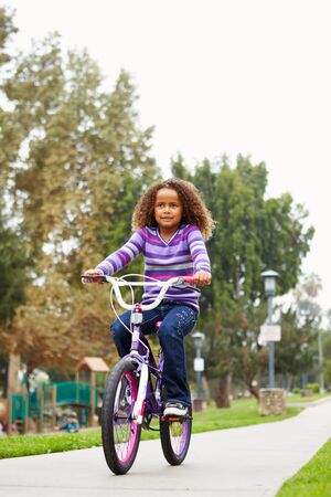 riding: Young Girl Riding Bike In Park Stock Photo