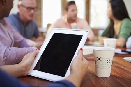 collaborating: Businessman Using Digital Tablet In Meeting