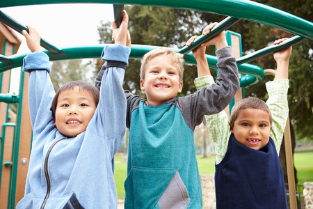 mixed race children: Three Young Boys On Climbing Frame In Playground Stock Photo