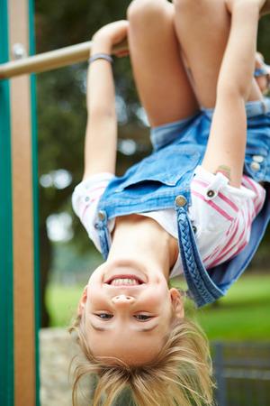遊び場でフレームを登山に若い女の子