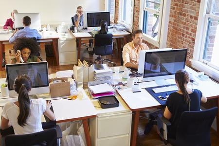team working: Grandangolo di Occupato Office Design con i lavoratori ai banchi Archivio Fotografico