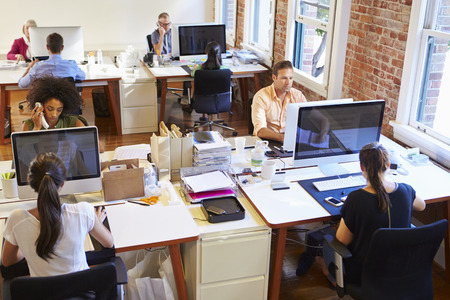 woman at work: Wide Angle View Of Busy Design Office With Workers At Desks