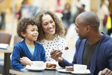 happy family shopping: Family Enjoying Snack In Caf� Together