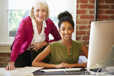 collaborating: Two Women Working At Computer In Contemporary Office Stock Photo