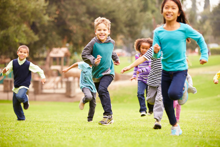 Group Of Young Children Running Towards Camera In Park 스톡 콘텐츠